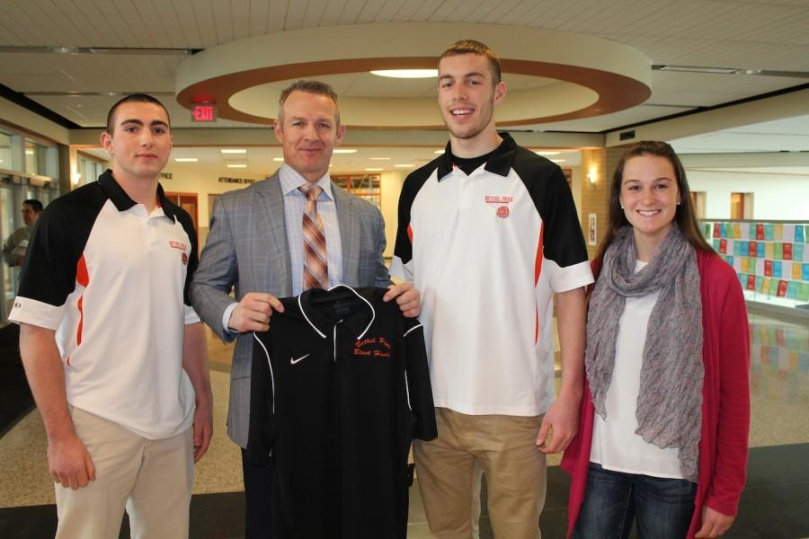 Students Levi Metheny, Jake Dixon, and Kelsey Tischler present Merril Hoge with a Bethel Park Black Hawks shirt.