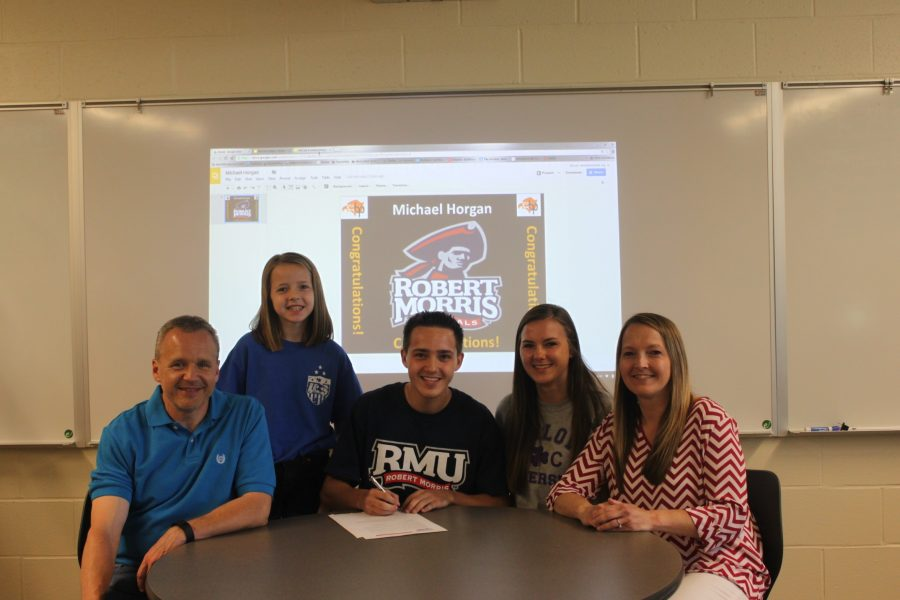 Michael Horgan, with family by his side, signs his letter of intent to play soccer at RMU.