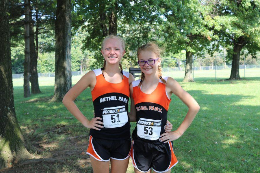 Hannah Crawford (left) poses with her friend and teammate Lilly Zeminski at a cross country race.