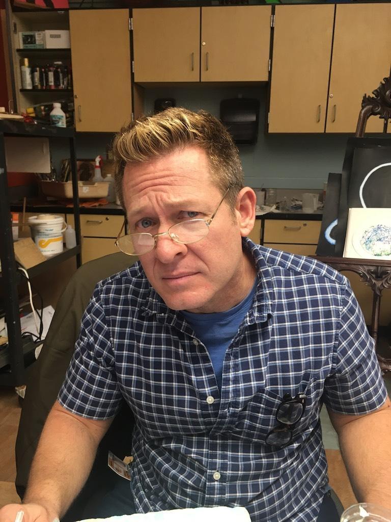Kent Wallisch modeling glasses at his desk.