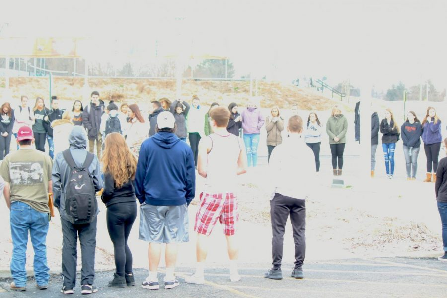 Students+gather+in+silence+around+the+flagpole+in+the+front+of+the+school+on+Wednesday%2C+March+14.
