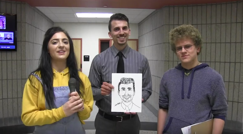 Senior Topher Futrell proudly stands next to his completed caricature of Mr. Allemang, while host Maria Cerro looks on.