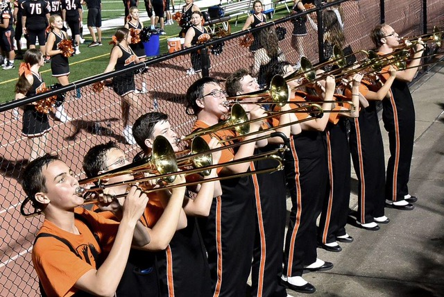 WITH THEIR ARMS ALL THE WAY EXTENDED, the Bethel Park Marching Band Trombone Section performs