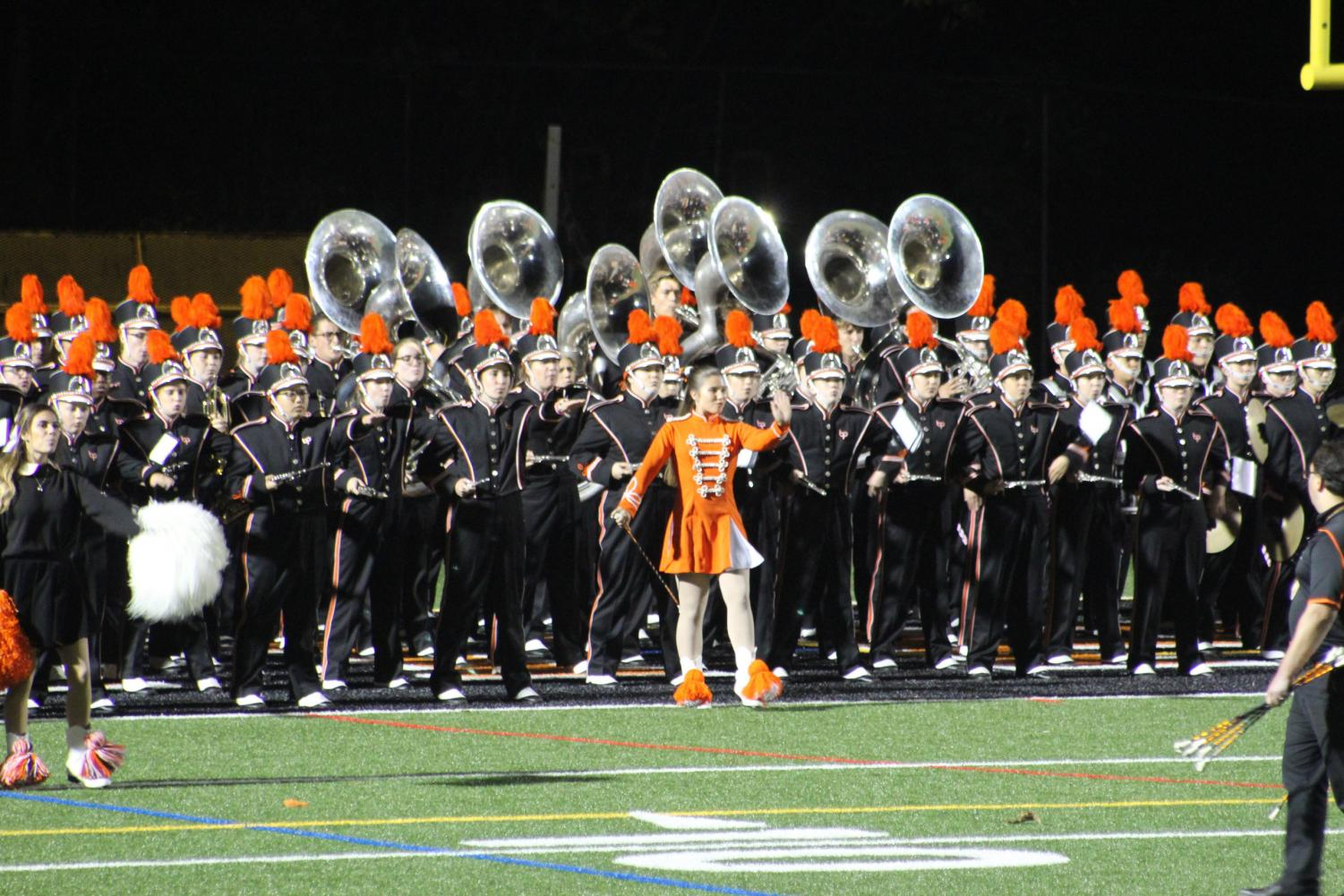 INSTRUMENTS RAISED, the Marching Band steps onto the field during halftime of a Hawks football game.