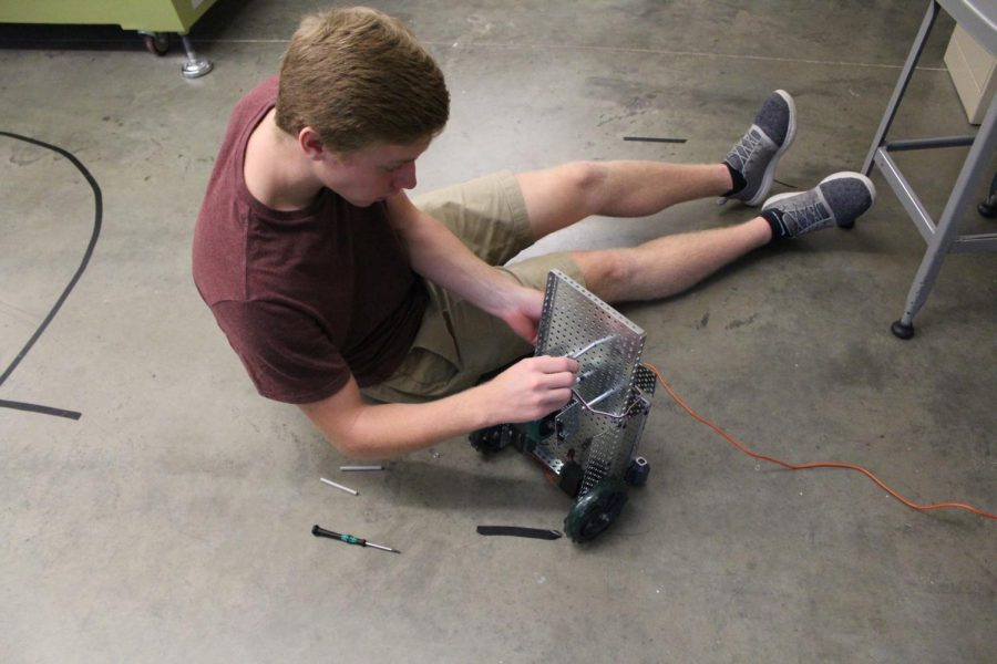 METICULOUSLY ADDING A FEW ADJUSTMENTS, senior Chris Toth preps his robot for testing.