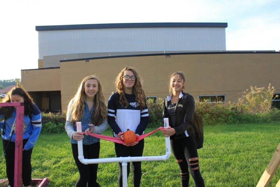 STANDING BESIDE THEIR LAUNCHER, Alex Cox, Isabella Pusateri, and Alexa Rooney smile for the camera moments before they launch their pumpkin.