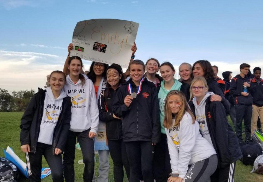 PROUDLY DISPLAYING HER MEDAL, Emily Carter poses with her teammates after her 3rd place finish at the WPIAL Championships.