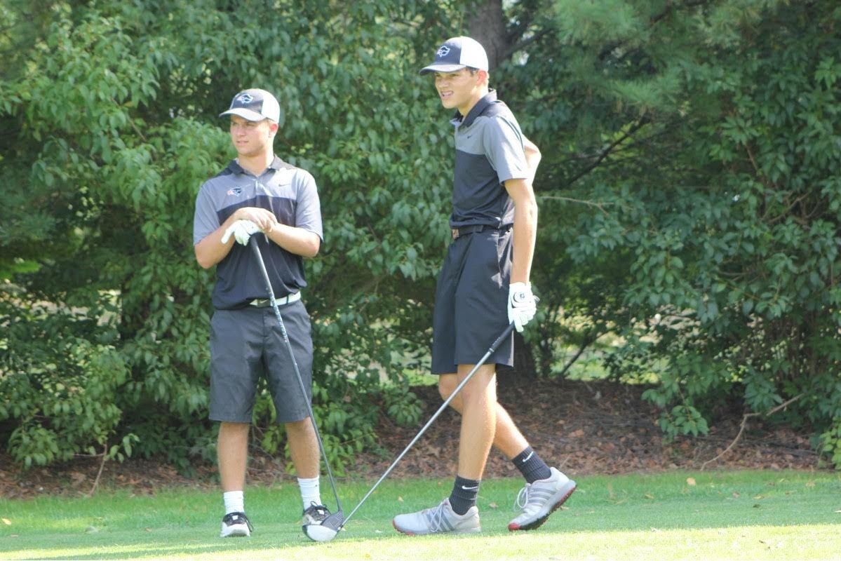 LOOKING IN THE DISTANCE, junior Parker Loera and sophomore Zack Sackett watch their drives after teeing off.