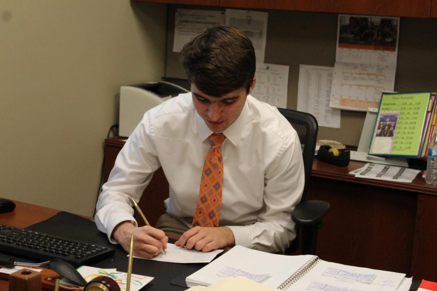 2018 grad Ty Miller works at Dr. J's desk.  Ty won Hawk Hunk and got to be Dr. J for a day.