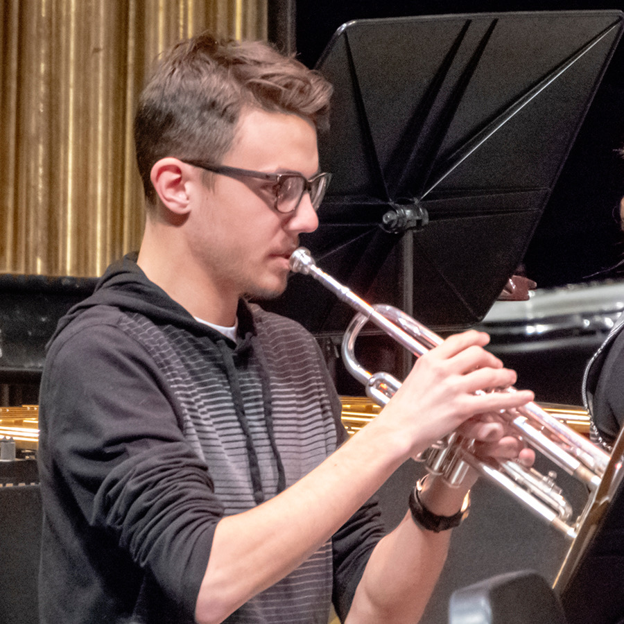 Junior+Aidan+Tarr+plays+his+trumpet+for+the+crowd+during+their+concert.