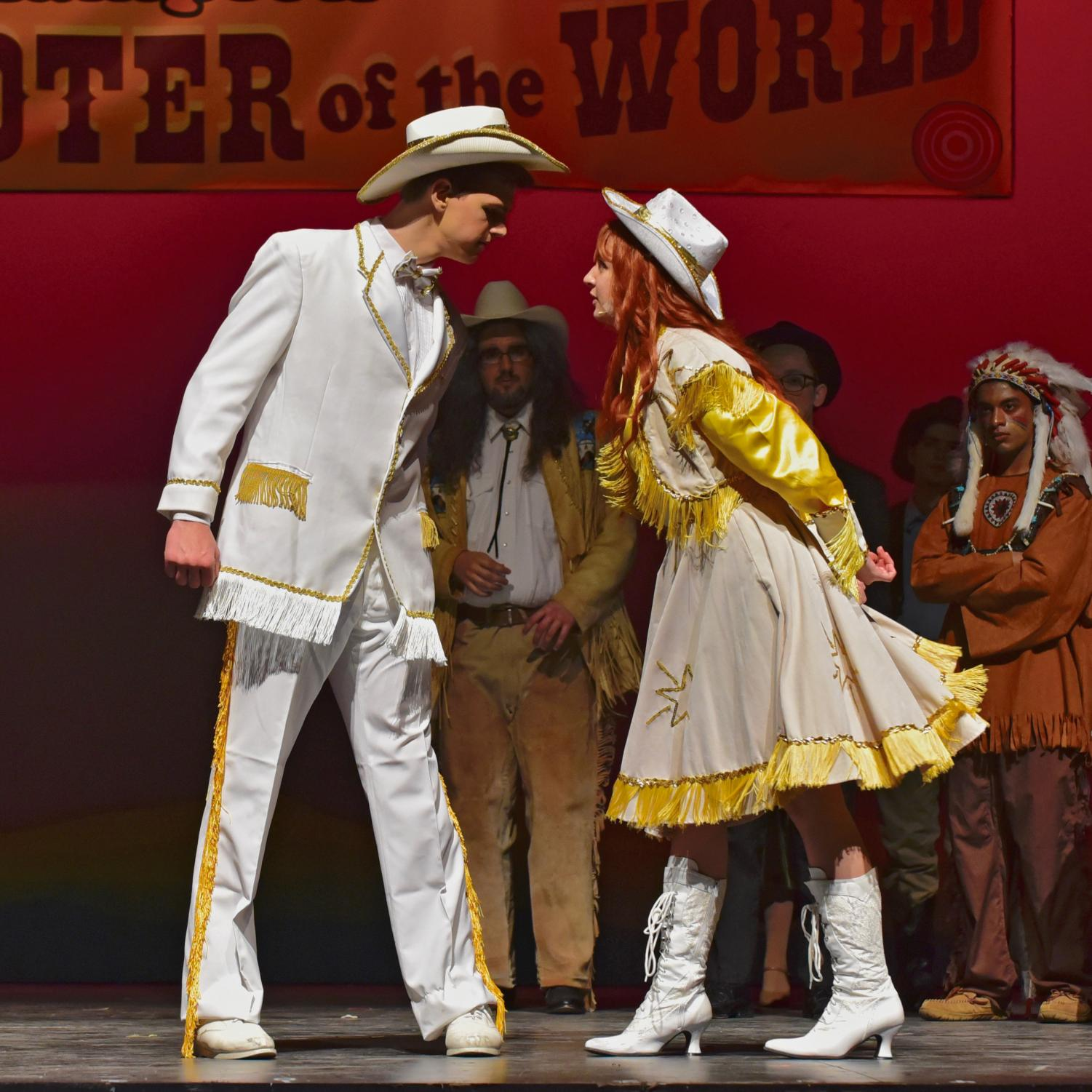 Collin McCormick as Frank Butler and Katelyn Marcovecchio as Annie Oakley duel on stage.