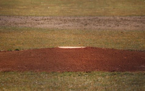 The pitching mound at Purkey Field lies in focus while a messy infield is seen in the background on Wednesday, March 27, a day after rain.