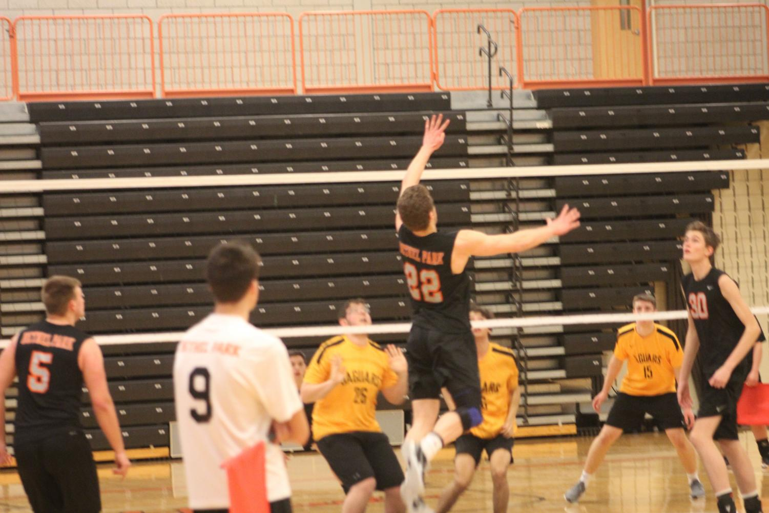 Max Cooley jumps to spike the ball during the Hawks' game vs. Thomas Jefferson on March 22. The Hawks won 3-0.