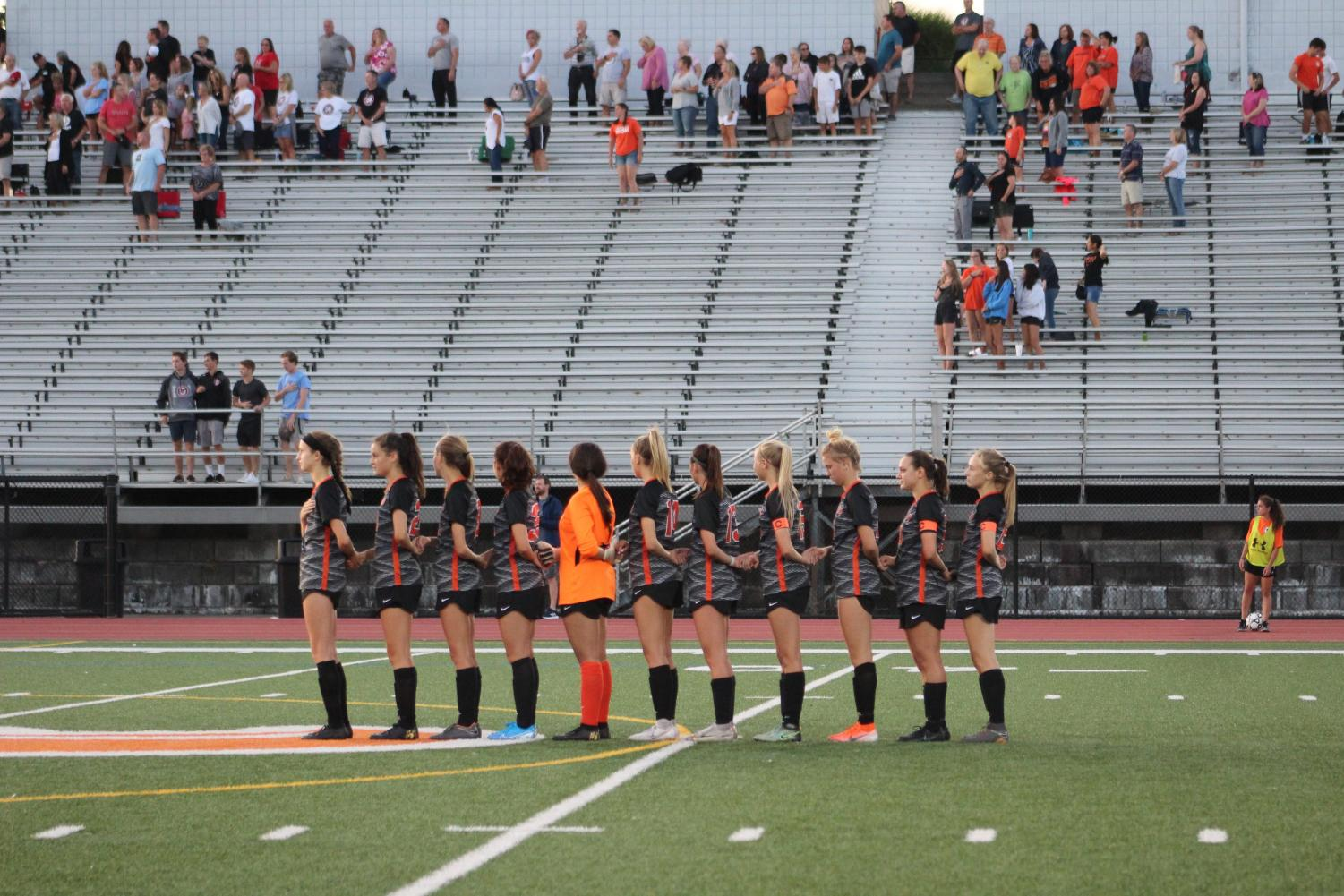 Lady Hawks stand in line during the National Anthem before their game against Peters on Wednesday, Sept. 4.