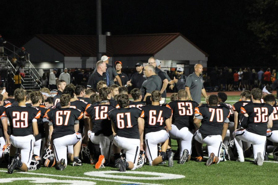 The varsity football players take a knee as Head Coach DeLallo talks to them after their win against West A on Friday, Sept. 6.
