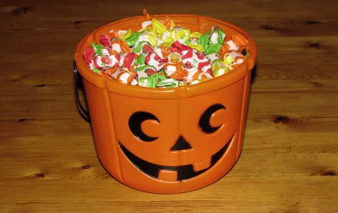 A Halloween candy bucket filled with candy.