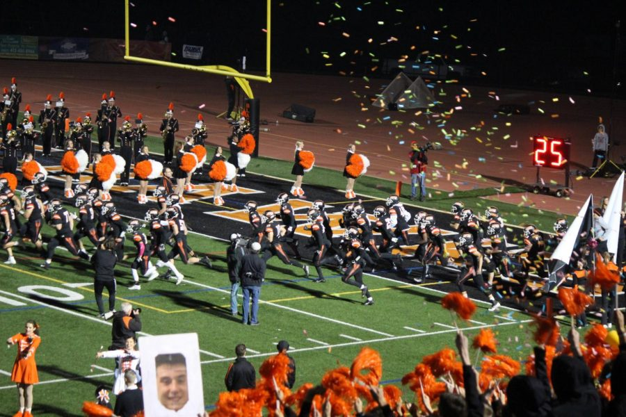 Among cheers and confetti, the football team, led by 21 seniors take the field for one of their last home games.