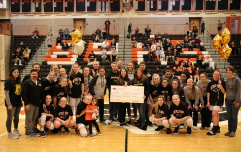 Lady Hawks present a check to the Fabus Foundation.