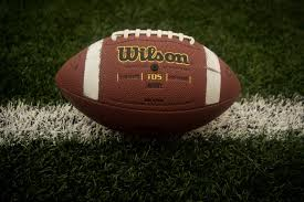 A picture of a Wilson football sitting on a football field