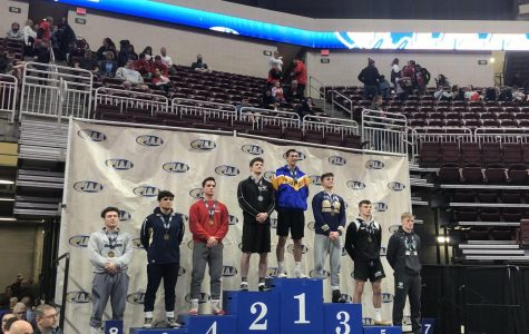 WITH A GRIN, Luke Montgomery stands for a picture on the podium after his second place finish at the PIAA Championships