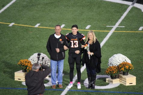 Anthony Chiccitt proudly stands with his parents on Senior Night on Oct. 18, 2019.