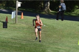 Jenna Lang runs up a hill at the Red, White, and Blue Invite at White Oak.
