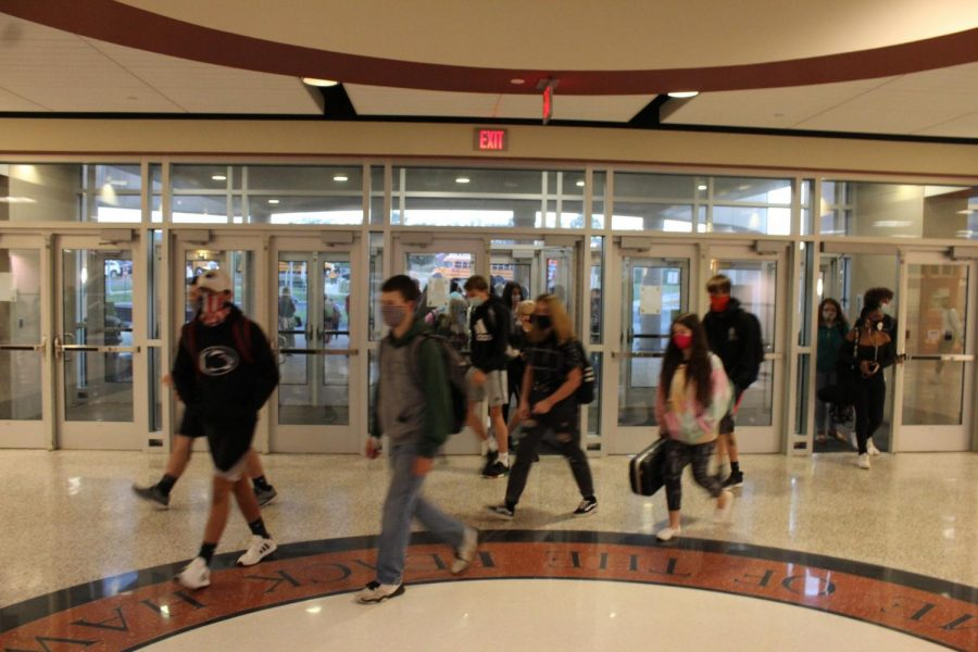 Students walk through the main doors of school on the first day of hybrid learning.