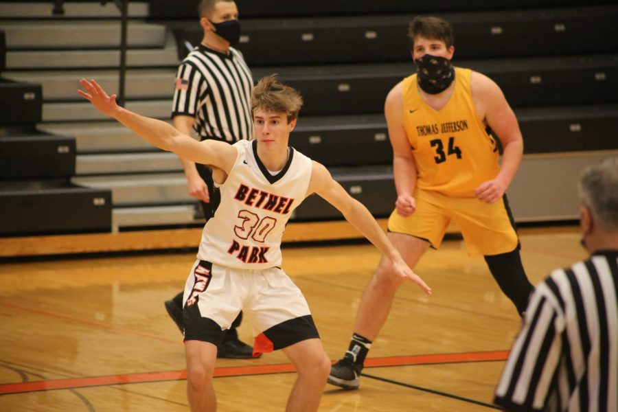 A TJ basketball player and the referees wear masks while a Bethel basketball player (John Harmon) does not. TJ requires its athletes to wear masks during competition. Officials are expected to wear masks. Bethel does not require its athletes to wear masks during active play.