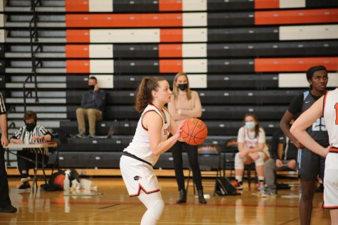 Emma Dziezgowski takes a foul shot as her coach and teammate look on.