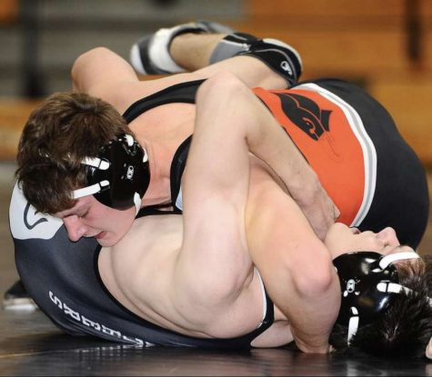 Senior Vinny Riepole pins his opponent during a match.