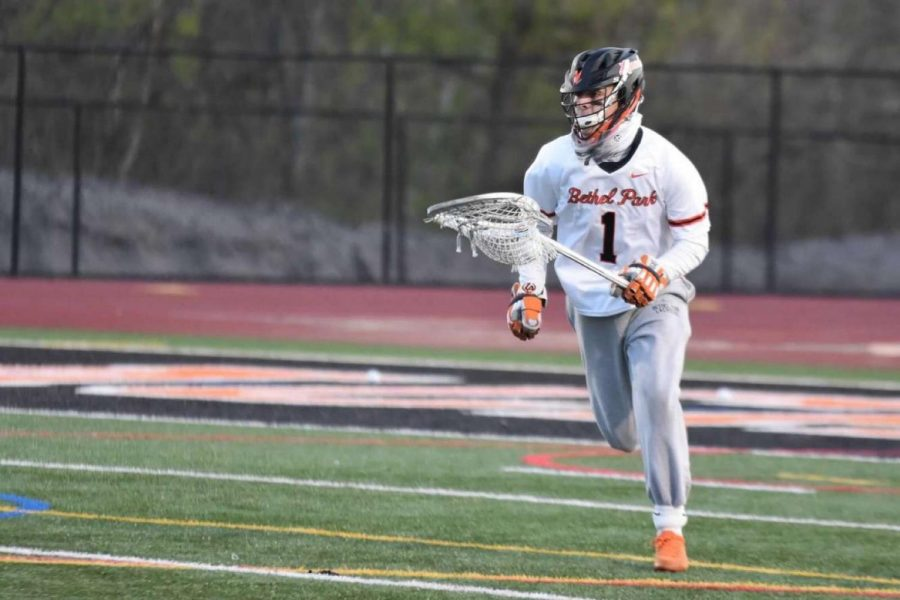Owen Peters running with the ball during a BP lacrosse game.