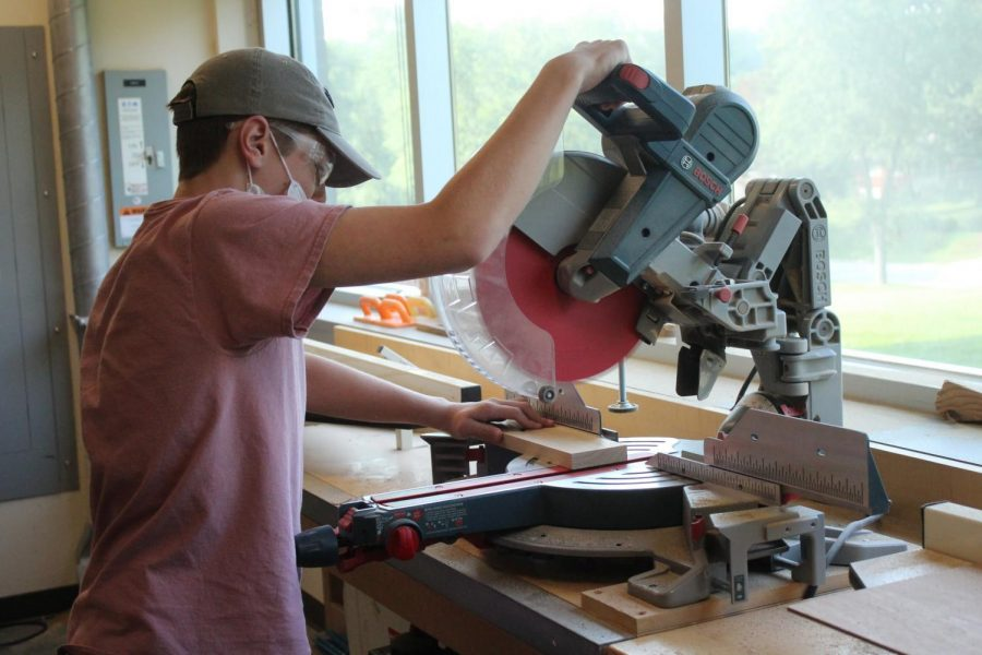 A student works with a table saw in Woodworking class.